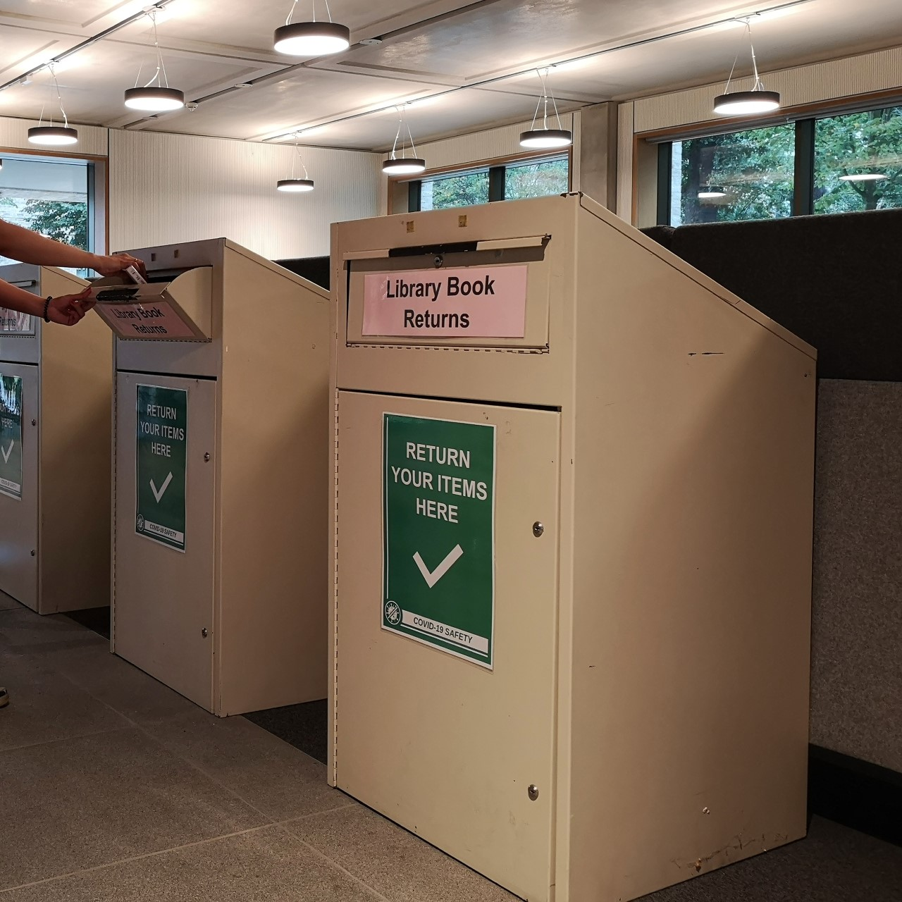 Three Book Returns bins in the Library foyer. The slot to put returned items into is at the top of each box.