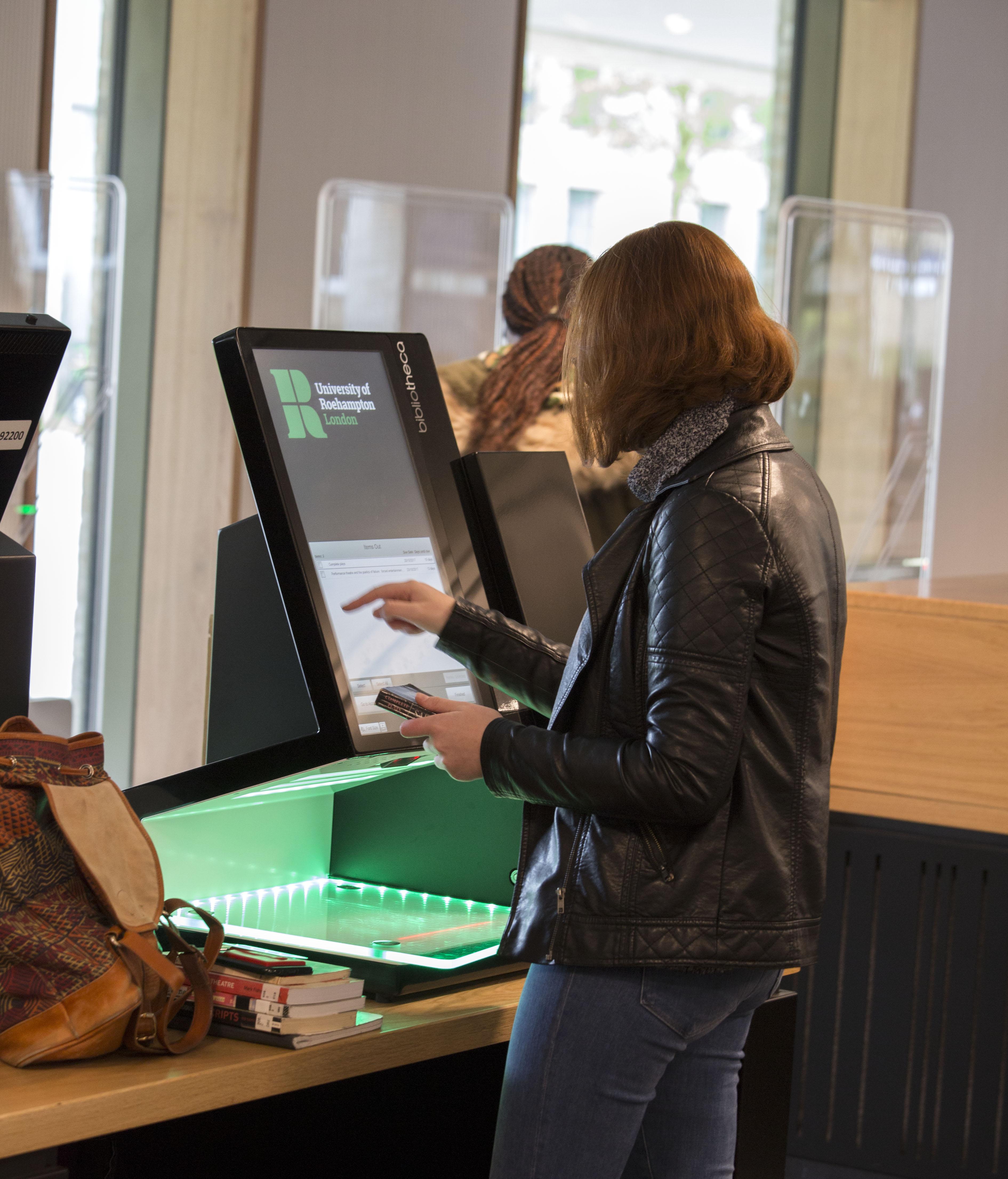 Student borrowing items using self service machine