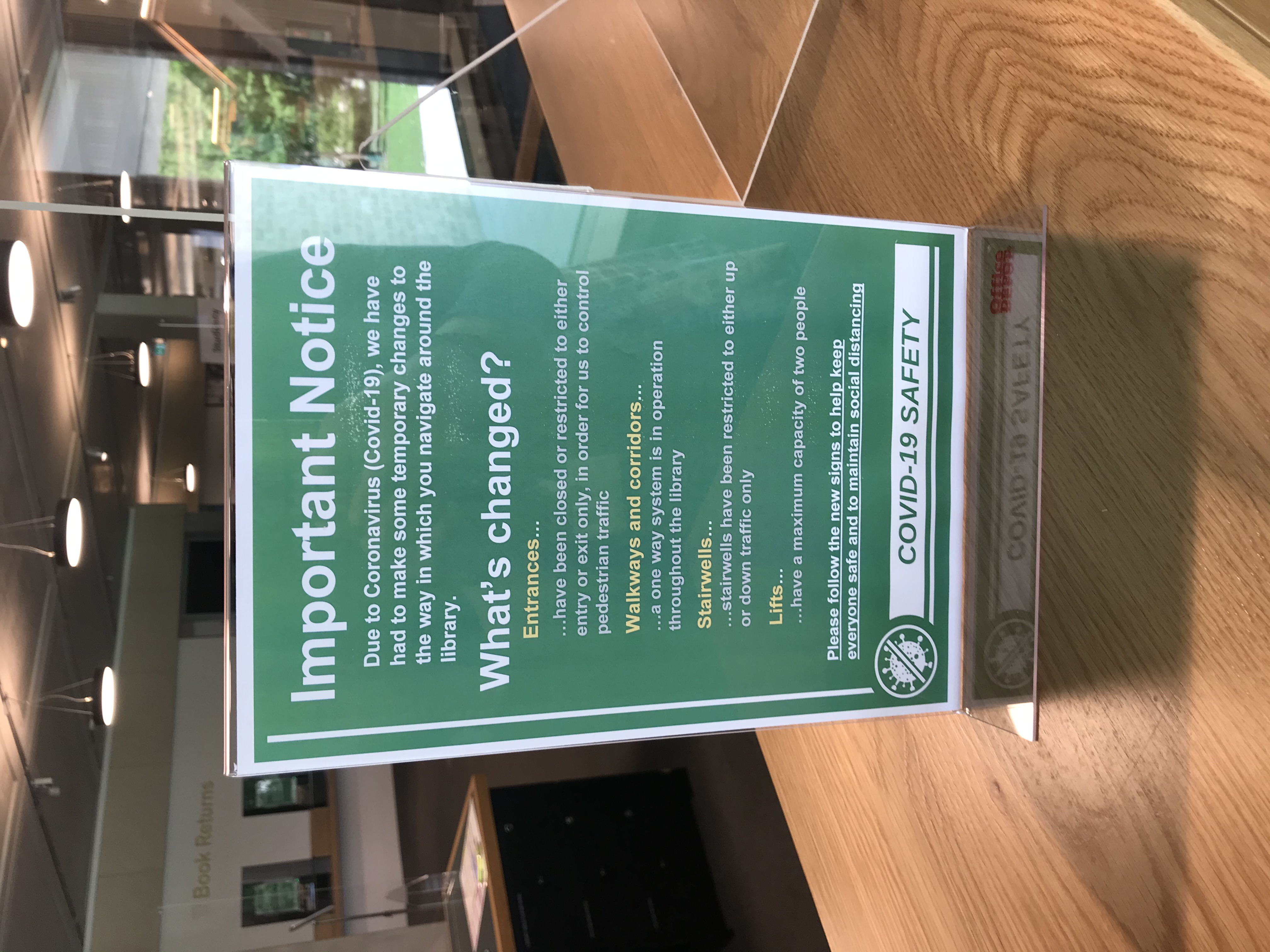 small sign on welcome desk with details of new procedures during covid-19