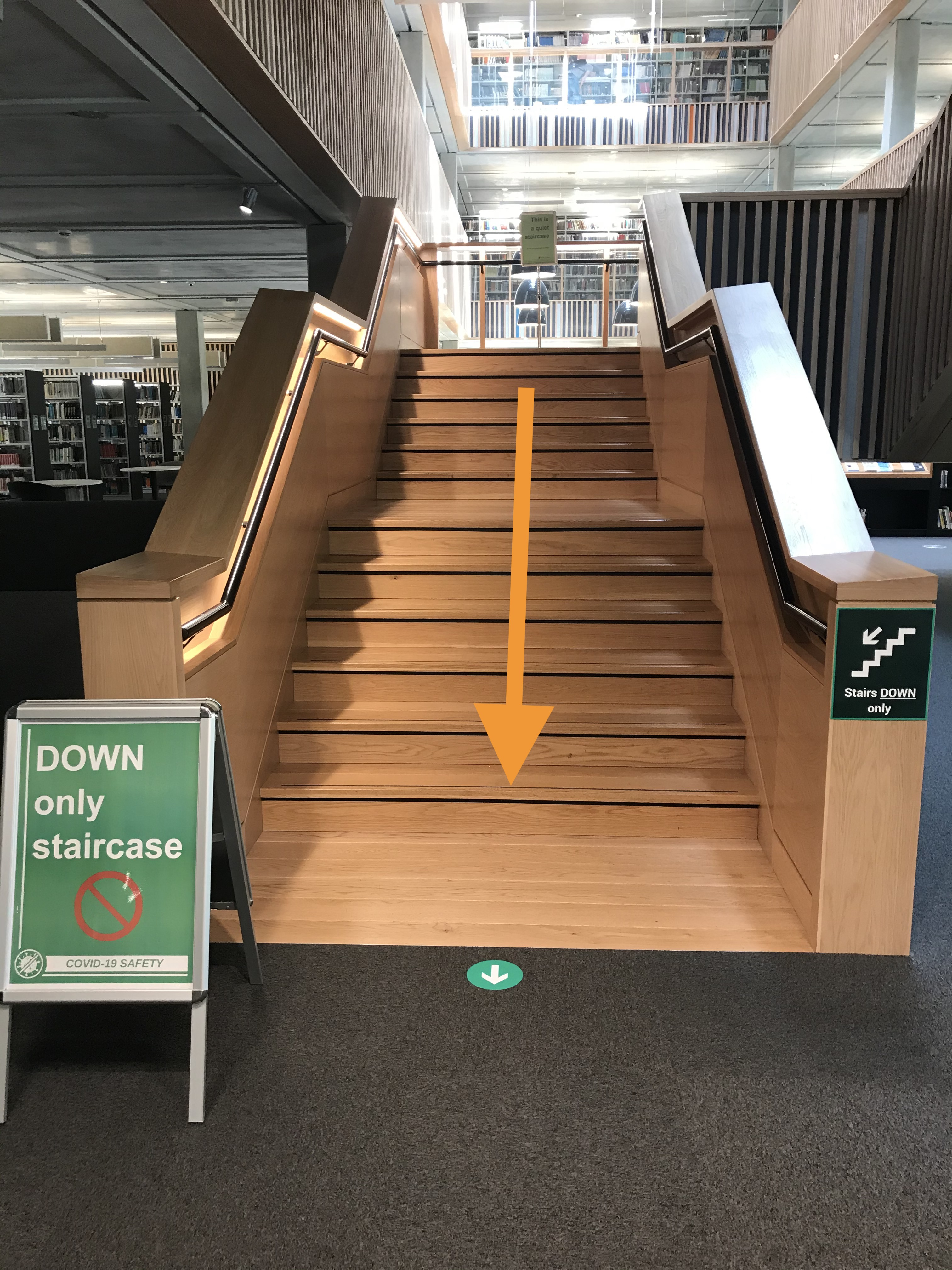 central wooden staircase with signage to show it is a Down staircase only
