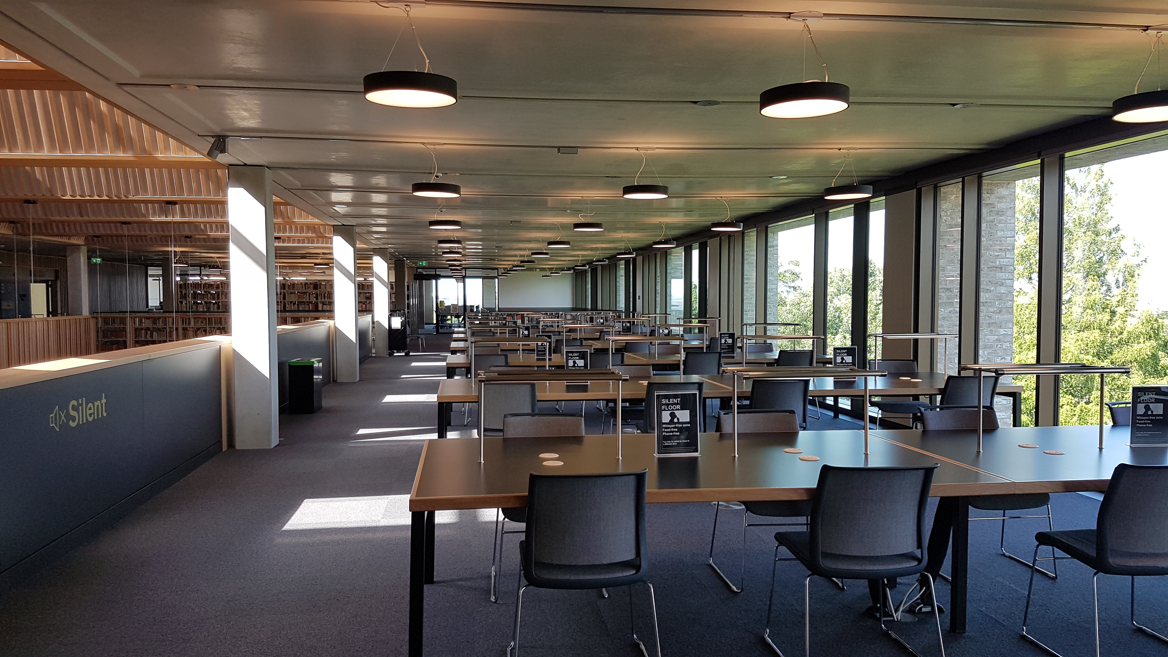 Study desks on the third floor between the atrium and windows. Each desk has 16 individual study spaces.
