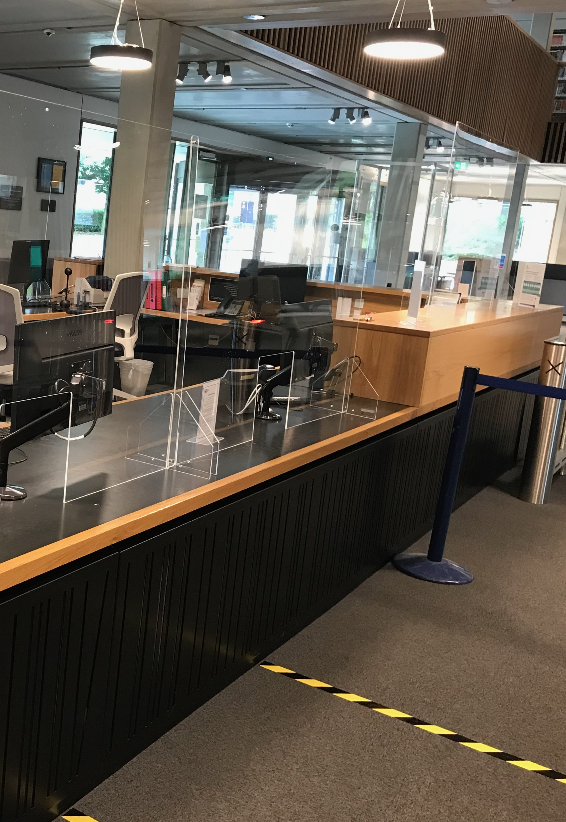 clear plastic barriers around the welcome desk to protect students and staff during social distancing