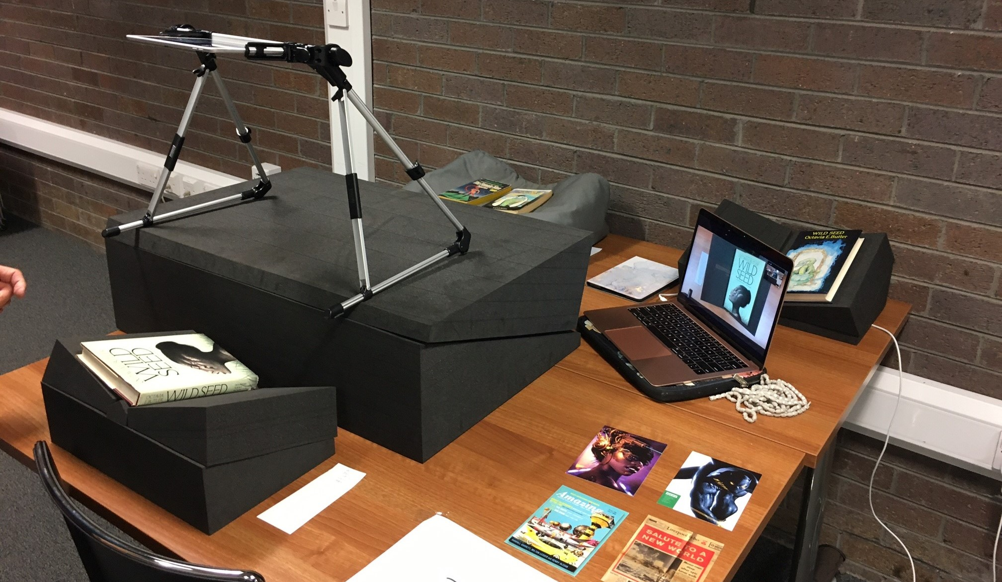 Teaching set up with books, iPad and laptop to stream collection items