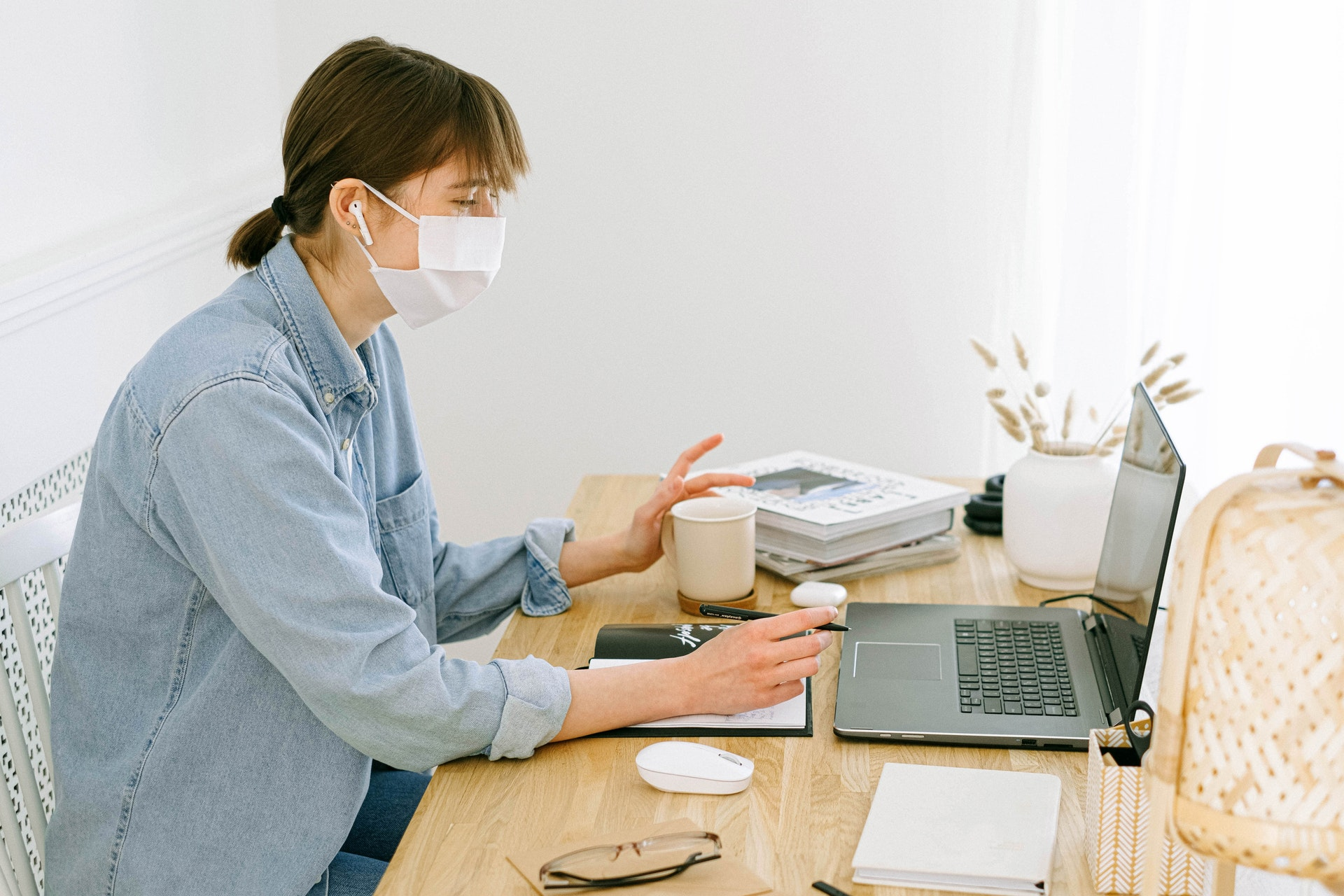 Woman using a laptop at a desk while wearing a white face mask