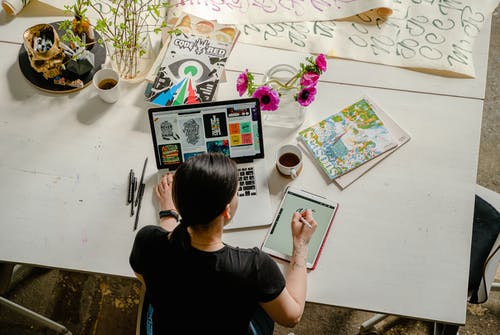 Woman drawing at a desk with a laptop and cup of coffee