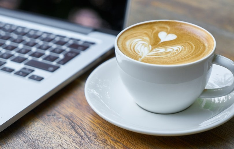 Cup of coffee next to a laptop