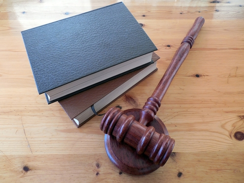 Books next to a gavel - a hammer used in a courtroom