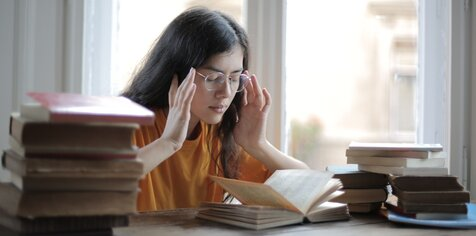 Student sat at a desk with piles of books