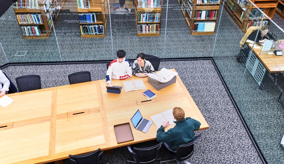 Users in the Barker Research Library looking at an item together