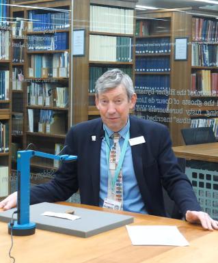 Archivist filmed with medieval deed in Palace Green Library