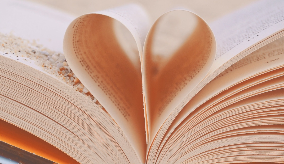 Open book with two pages turned in to the spine to make a heart shape