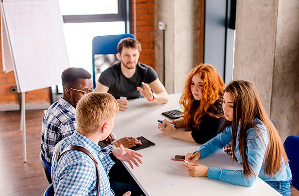 Ryhmä opiskelijoita istuu pöydän ympärillä