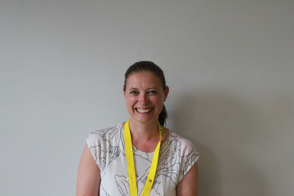 A friendly, smiling member of library staff wearing a yellow lanyard.