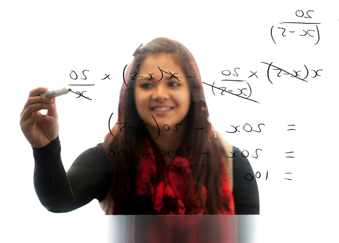 Student solving a Maths problem on a transparent board