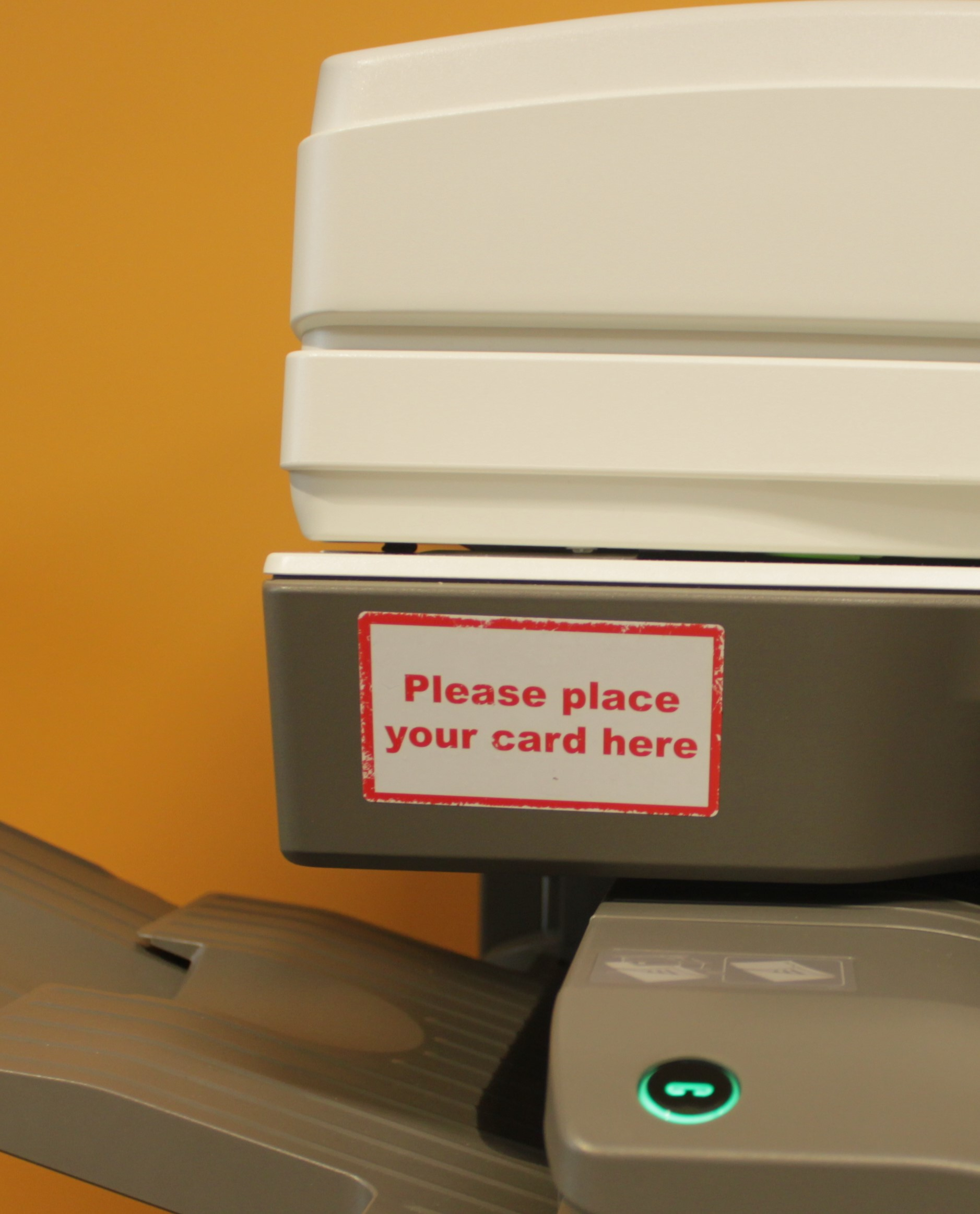 Image shows the location ID cards must be held to log in to the printer. Near the top of the printer, on the left-hand side. A label reads 'please place your card here'.