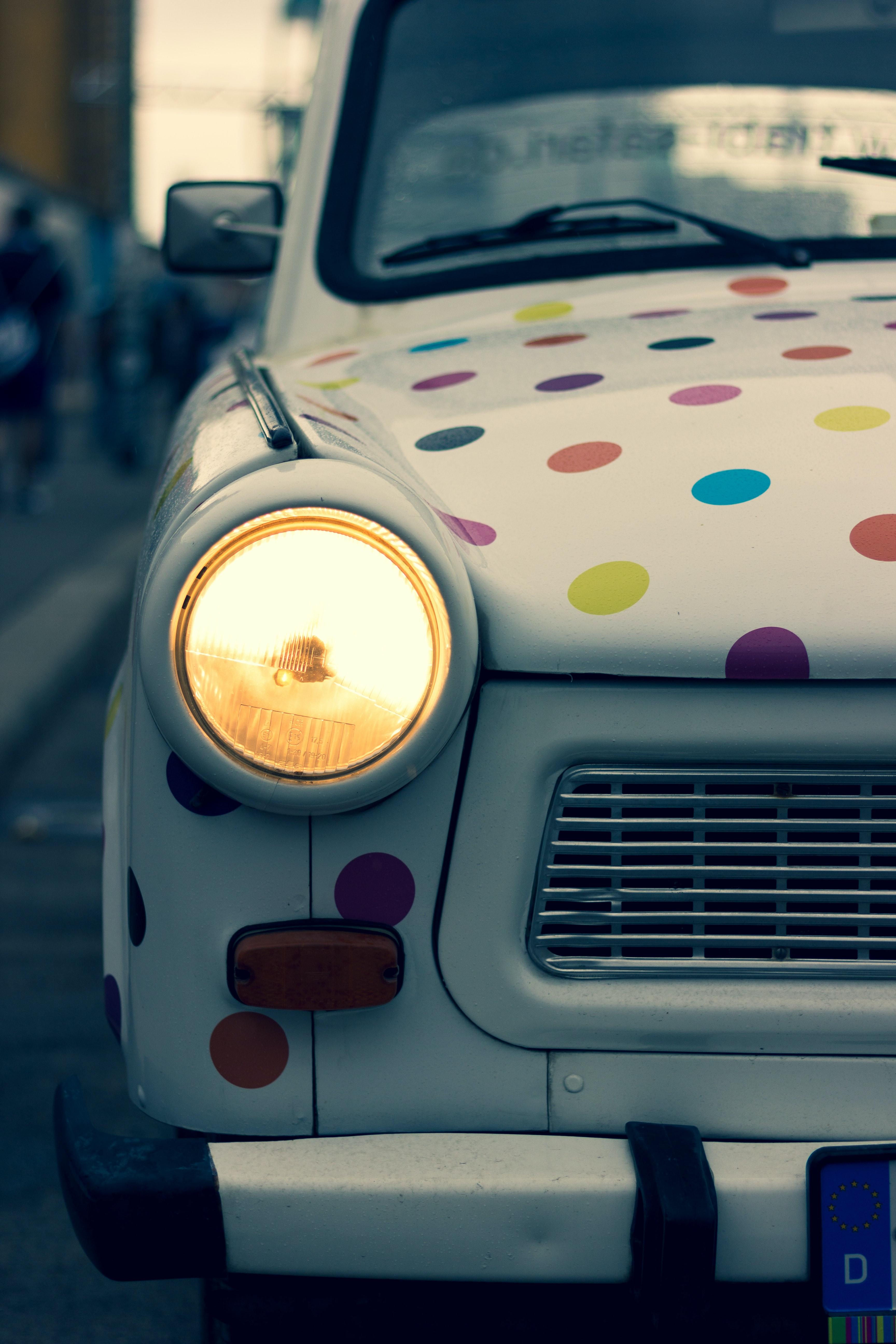 White Mini Cooper car, with multi coloured polka dots