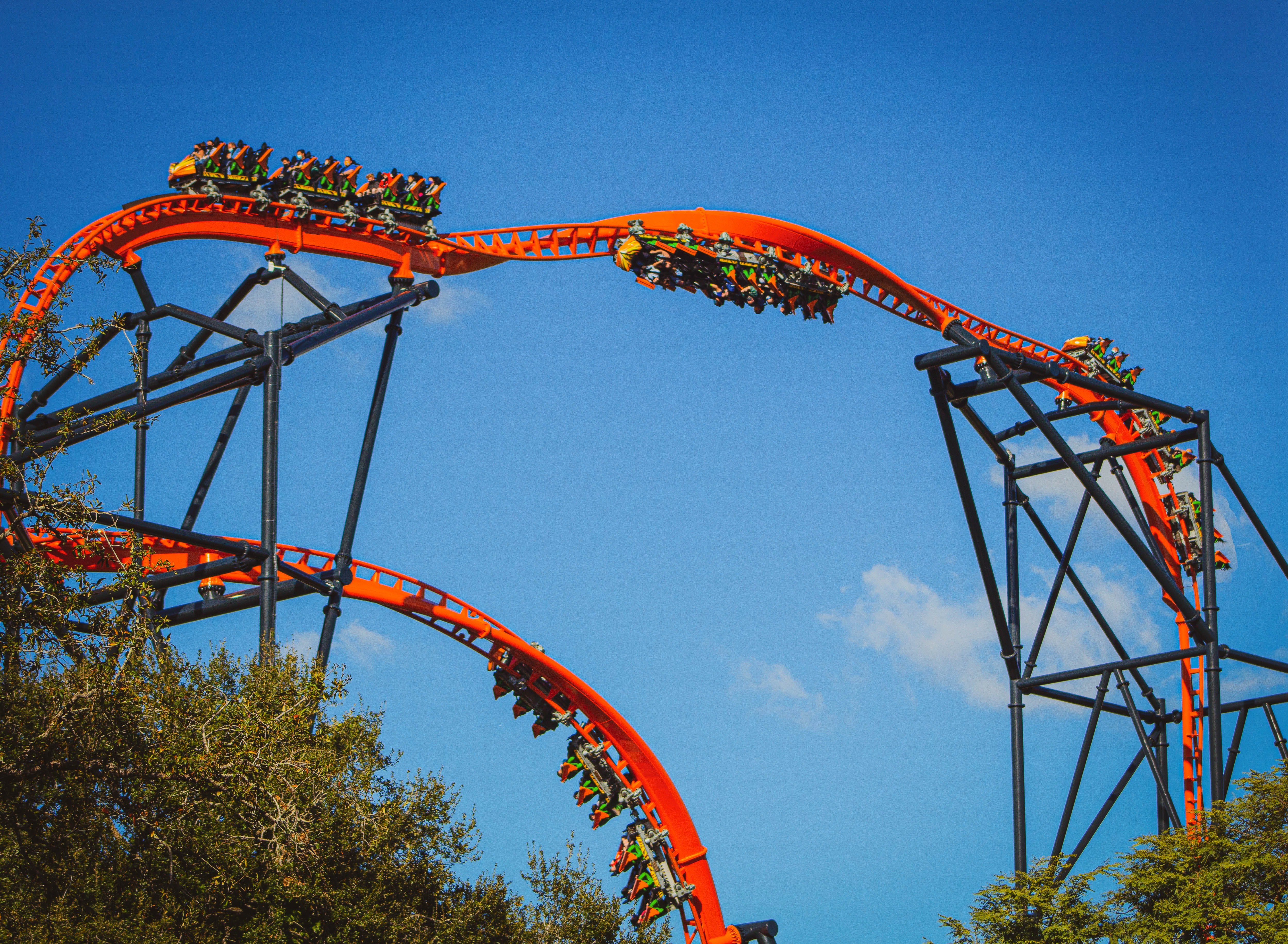 A huge red roller coaster with lots of carts moving round it. Lots of twists and turns.