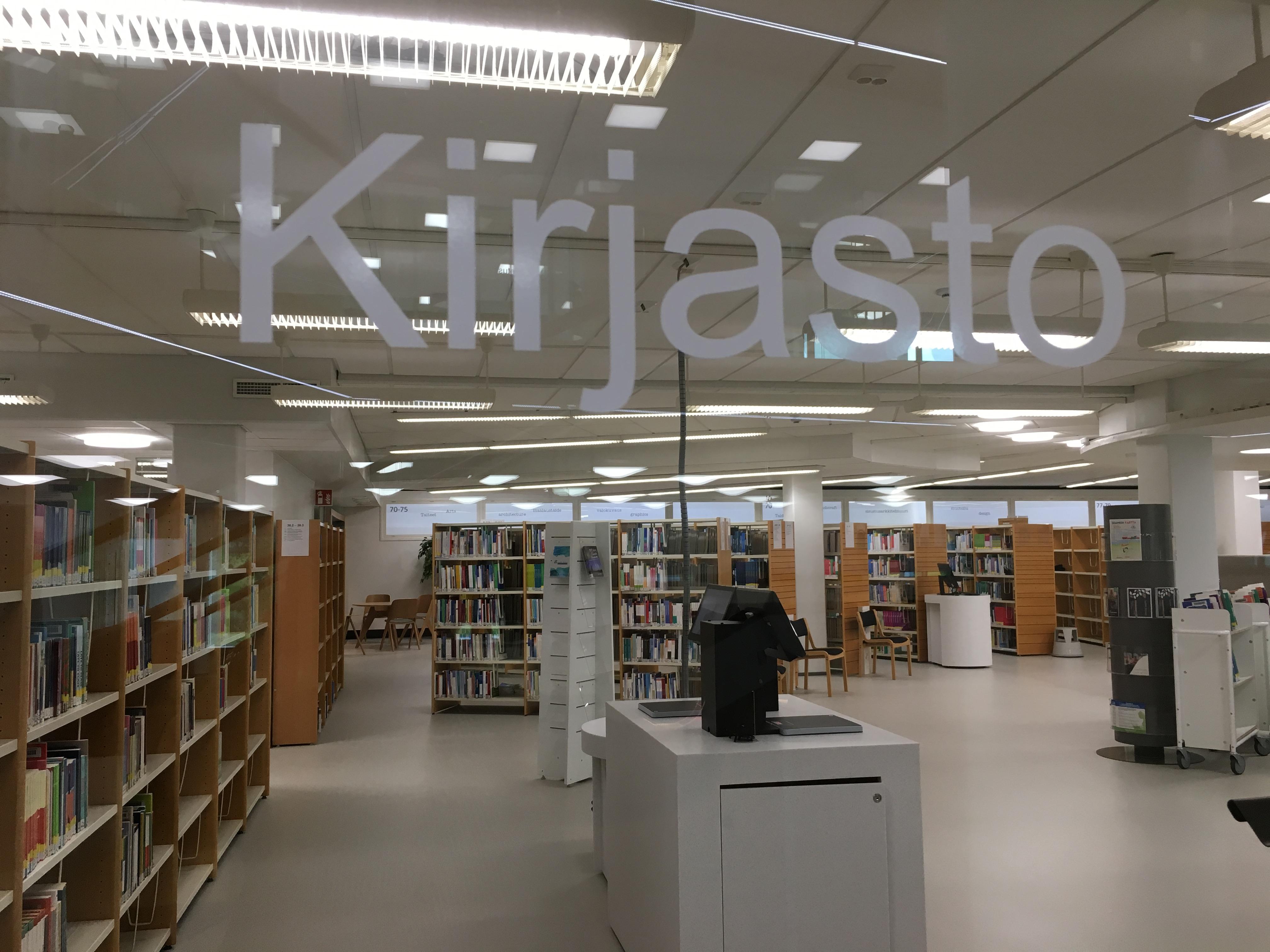 Kirjaston lasiovi jonka läpi näkyy kirjahyllyjä.