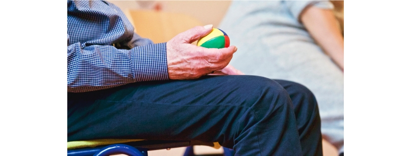 an elderly man holding a stress ball