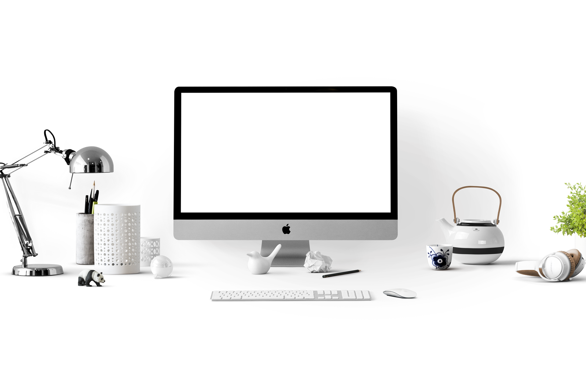 Apple desktop computer in the centre of a workspace. On the left is a silver anglepoise lamp and a pot of pens to the riht os a japanese teapot.
