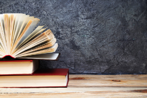 Two books lying flat on a desk, with a third one on top with its pages spread open forming a semi circle.. Click to view your subject guide and information on referencing and finding resources