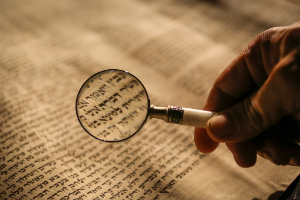 An image of a magnifying glass inspecting an historic document. Click here for information about library services offered to alumni and external visitors.