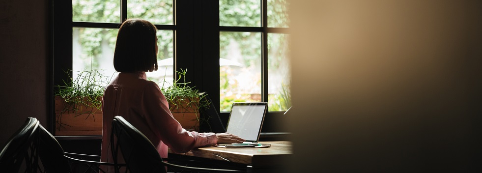 Female writer sat in front of a large window