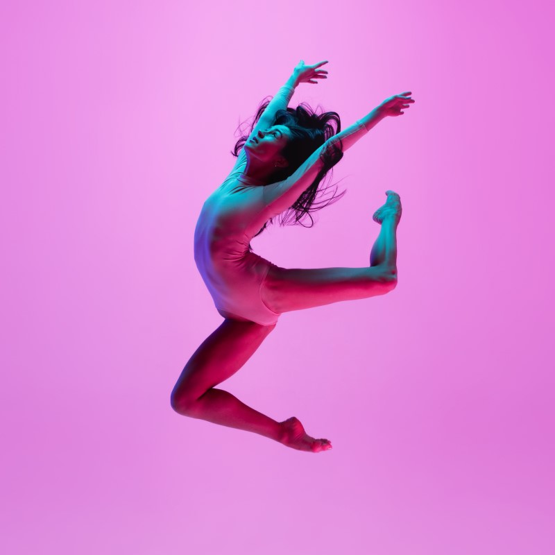 Jumping female dancer against a pink background