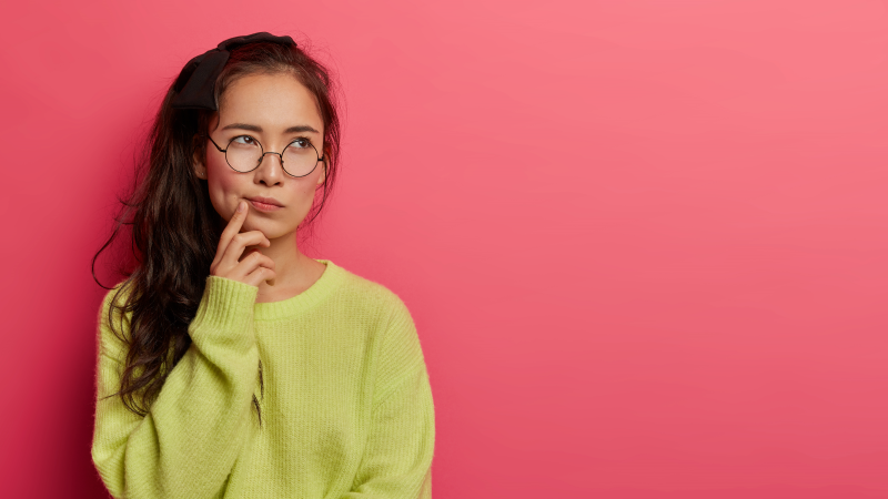 Female asian student looking thoughtful and pensive on a bright red background