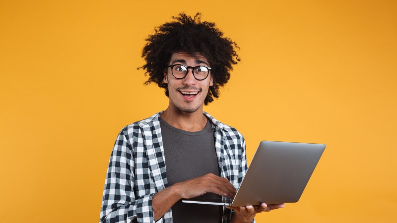 Happy young man in glasses with laptop