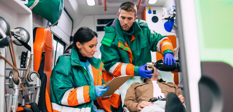 Two paramedics attending to a patient in the back of an ambulance