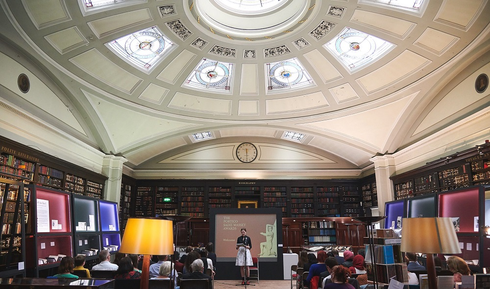 A female speaker reads in front of an audience under an ornate domed roof in Manchester's Portico Library