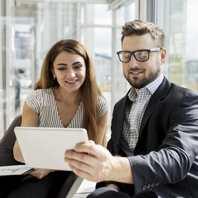 Two business people in smart clothing reading a tablet