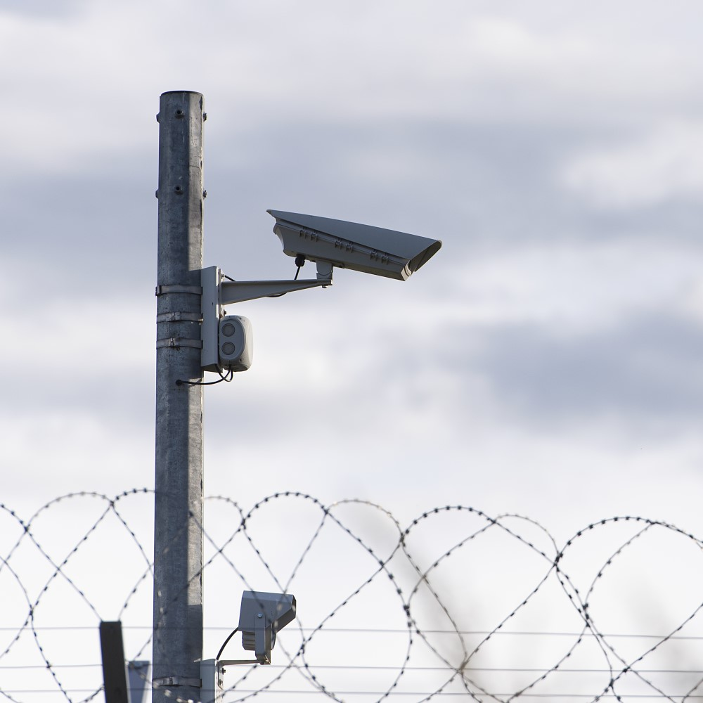 A security camera on a post over a barbed wire-covered wall