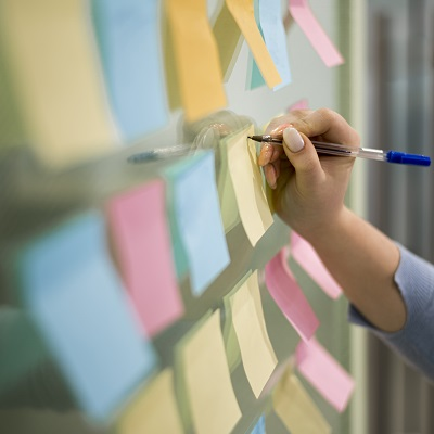Woman writing ideas on post-it notes on the wall