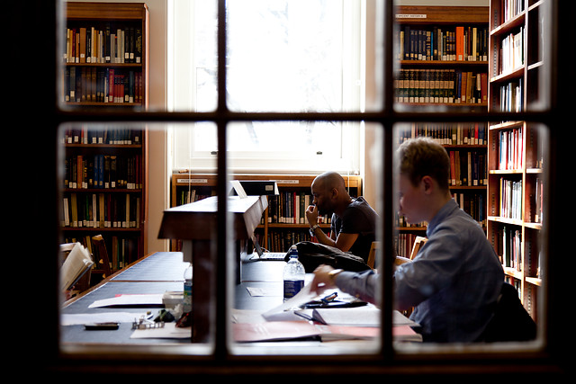 Students studying in a library reading room.