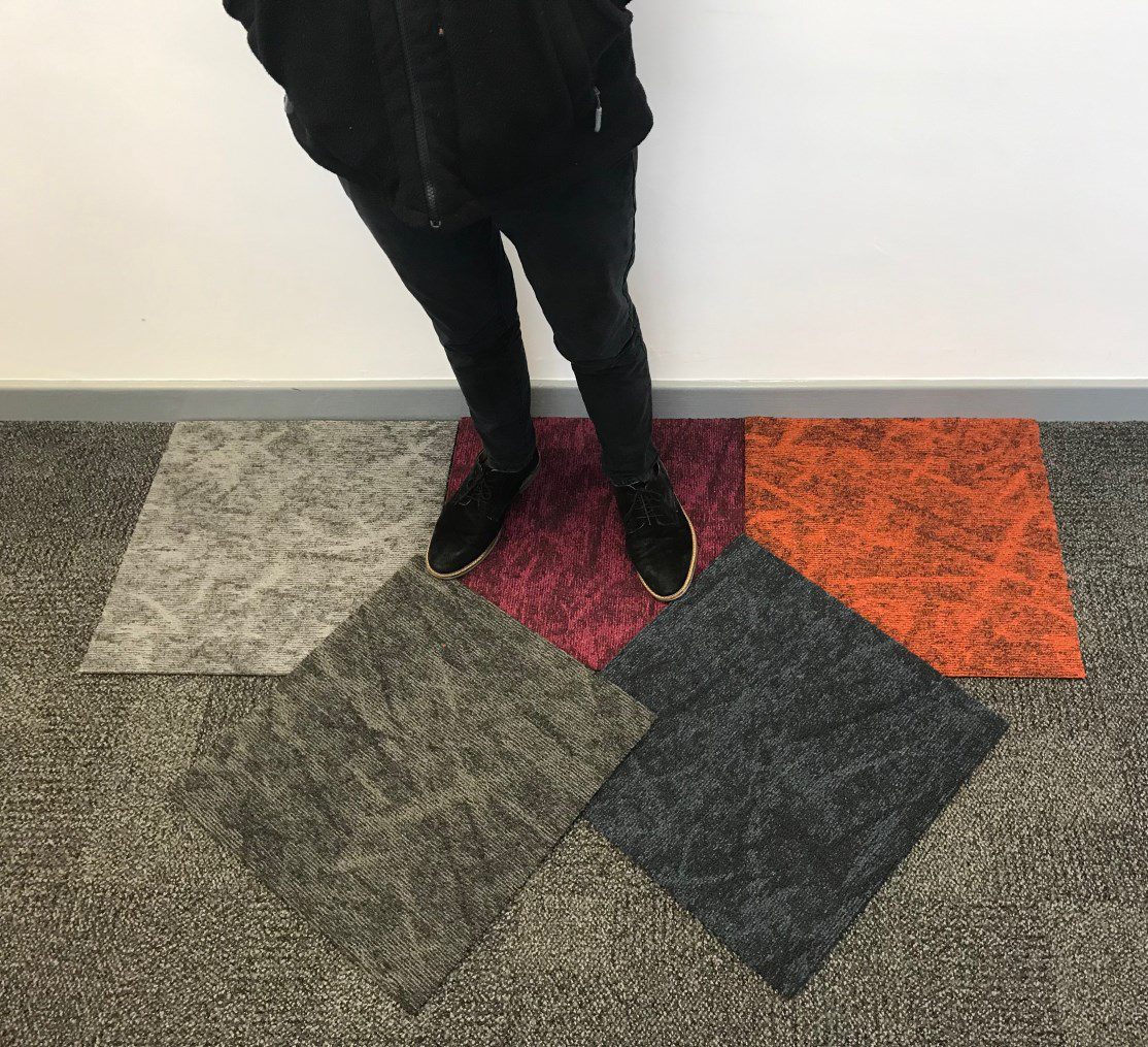 Man standing on a selection of different coloured carpet tiles