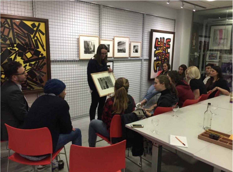 Joanne Harwood, Assistant Director, showing students some artworks